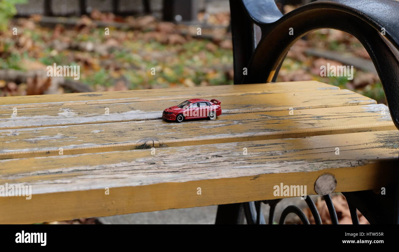 A single red toy car abandoned on a bench in the park - Stock Image