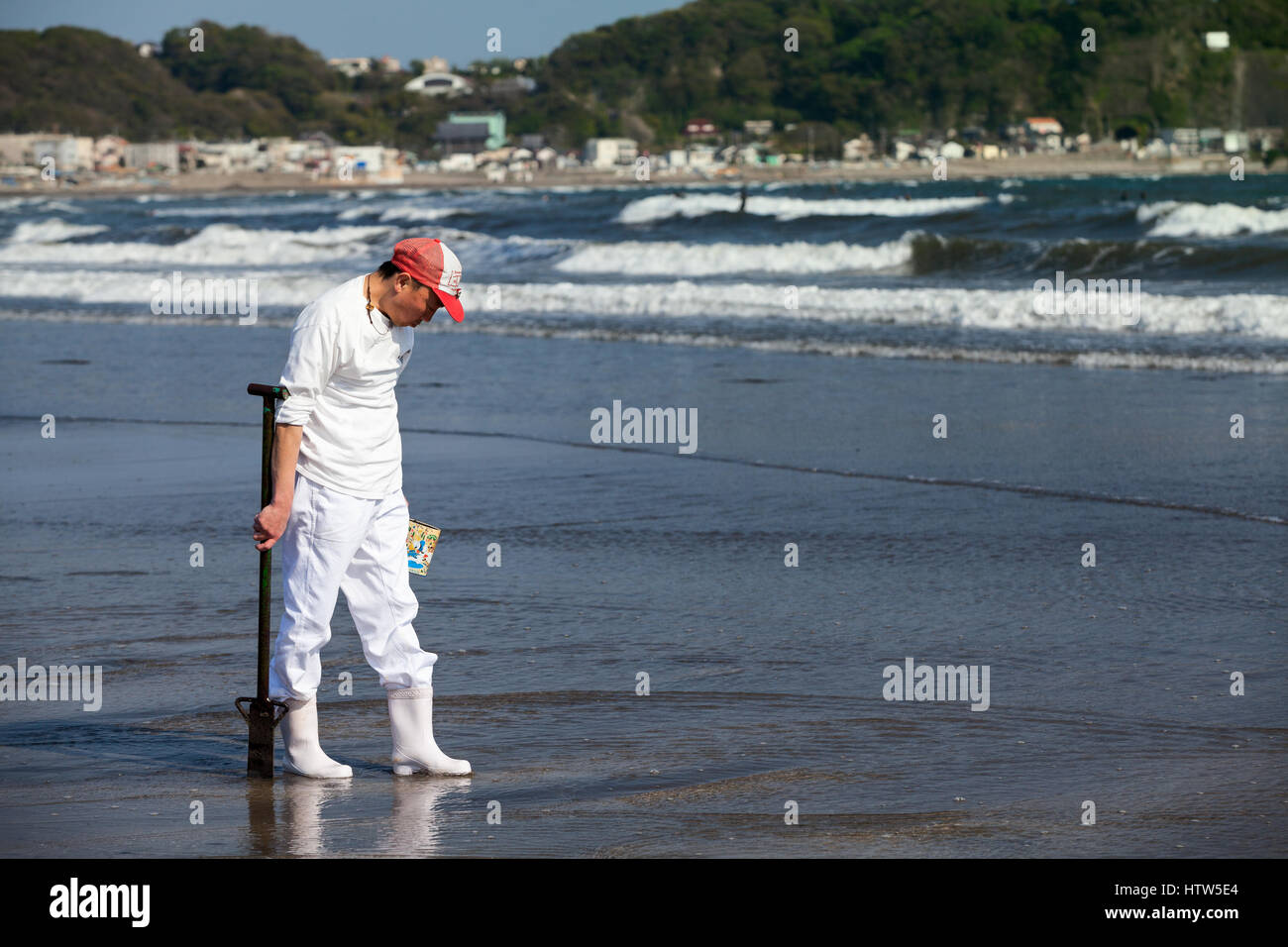 KAMAKURA, JAPAN - CIRCA APR, 2013: Japanese man finds sea food after high water on shallow in Nagai beach. Low tide Stock Photo