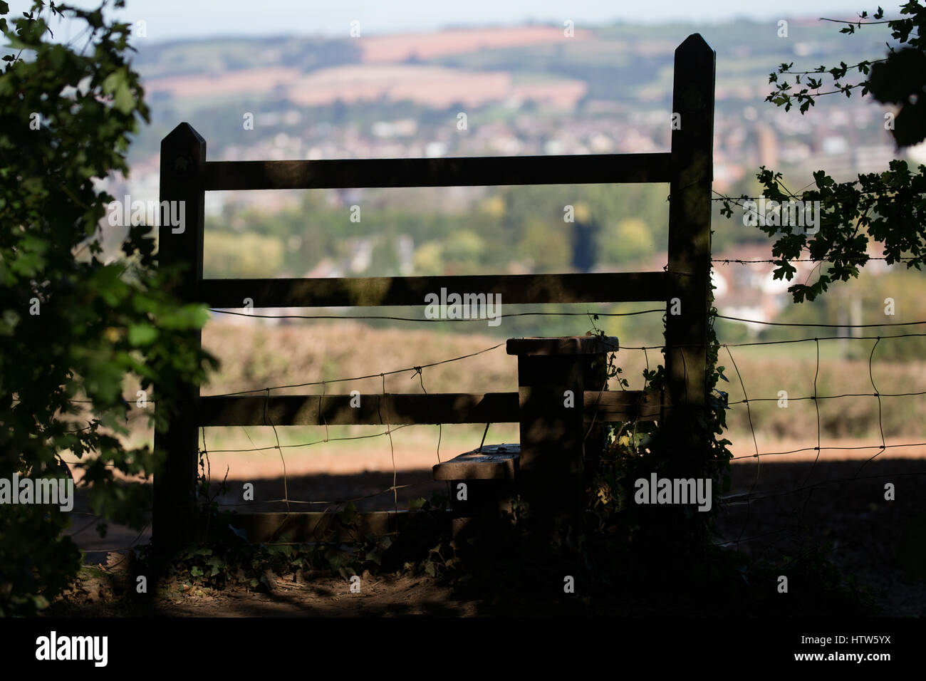 The view of the town of Taunton through a stile at the top of Cotlake Hill in the Somerset countryside. - Stock Image