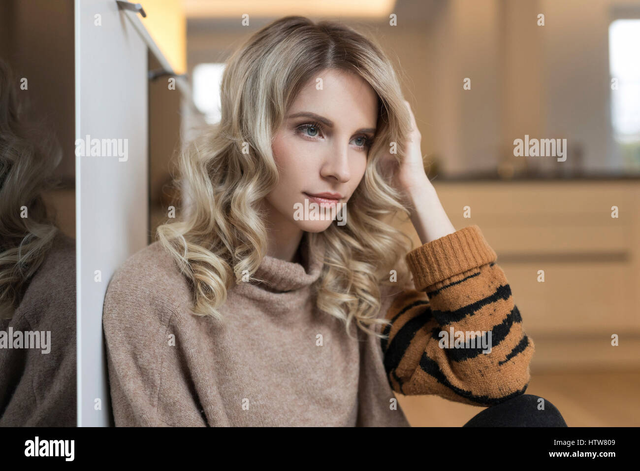 Portrait of a blond woman in the kitchen - Stock Image