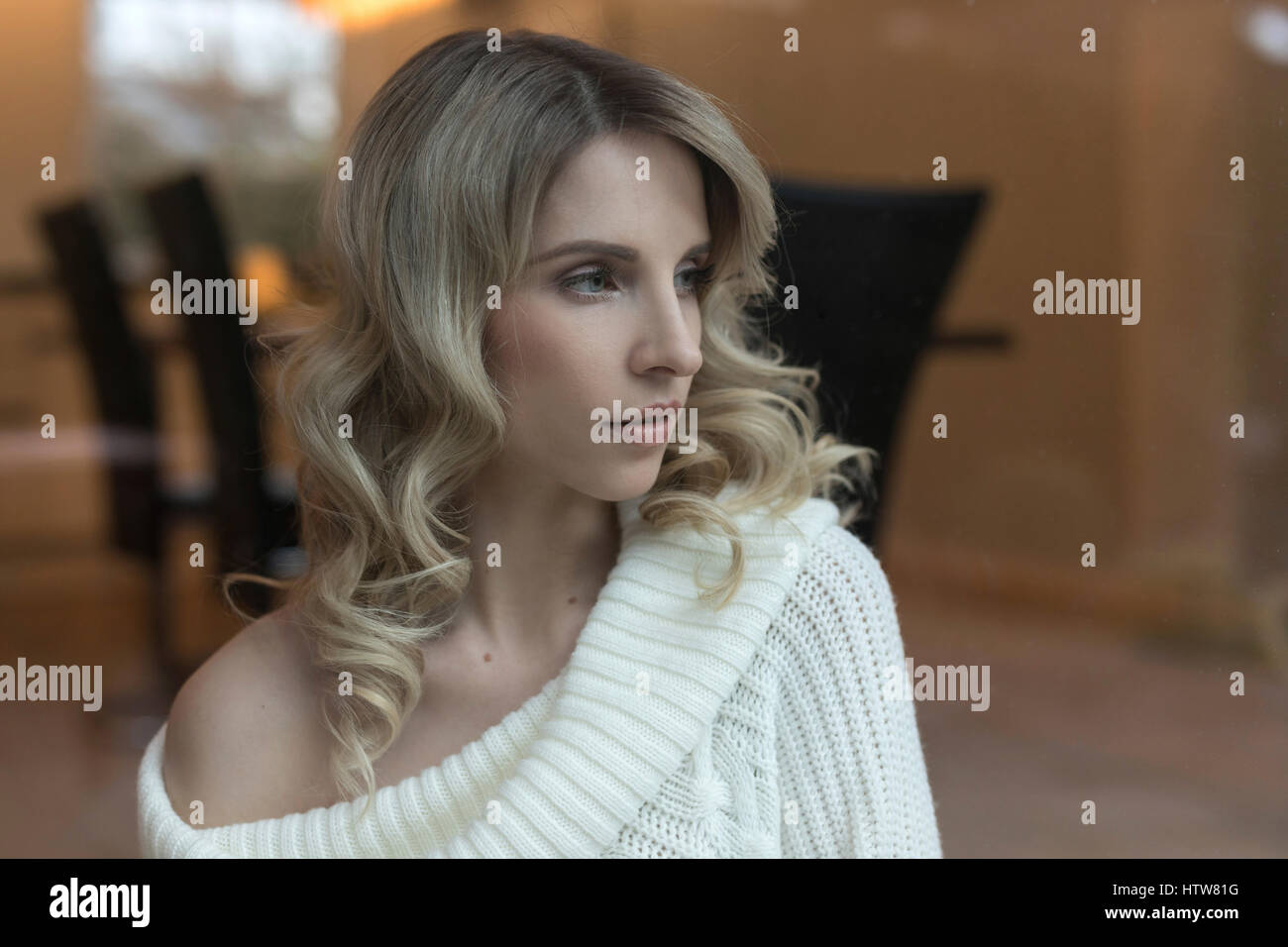 Portrait of a blond woman in the dining room - Stock Image
