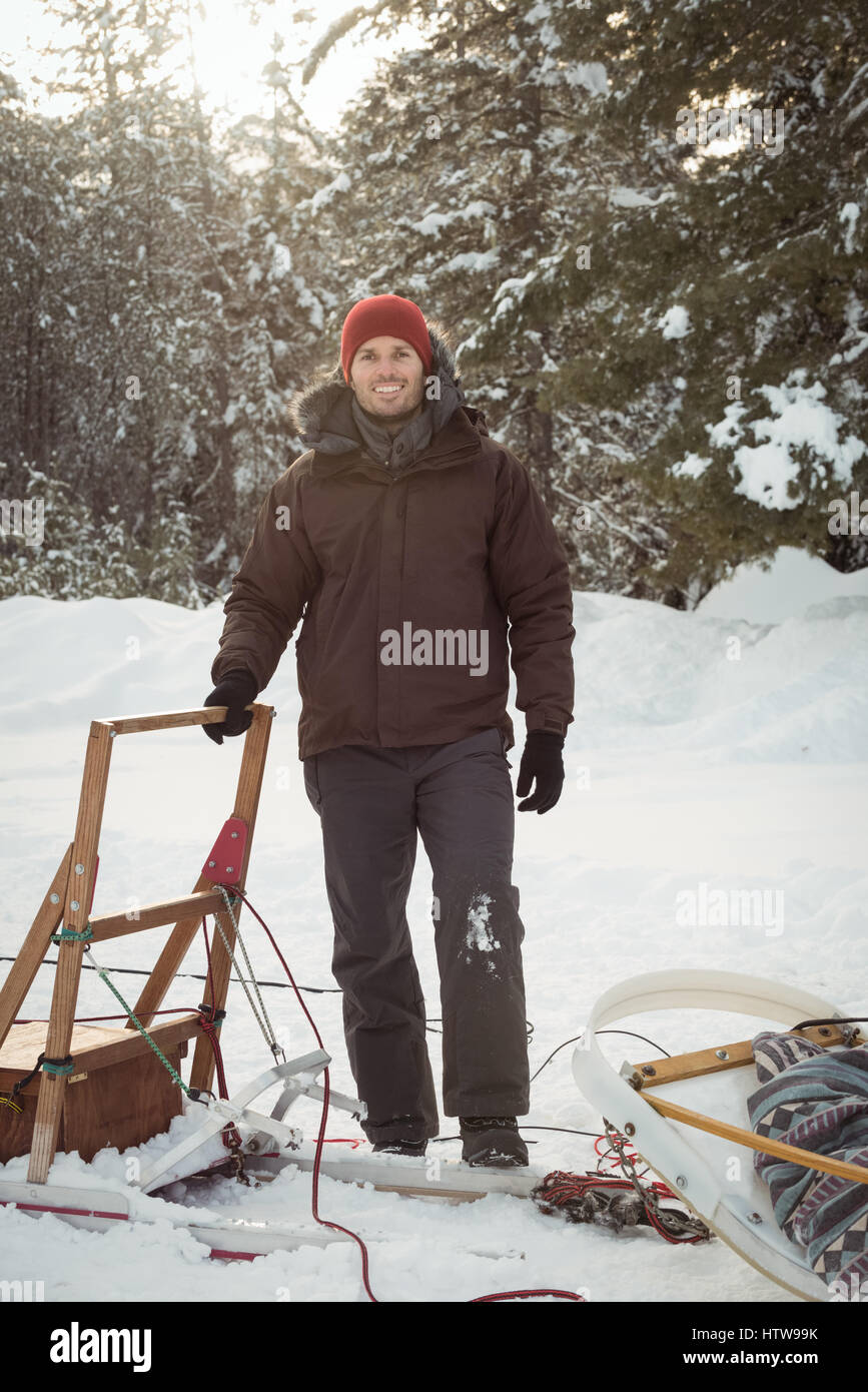 Male musher standing beside sleigh - Stock Image