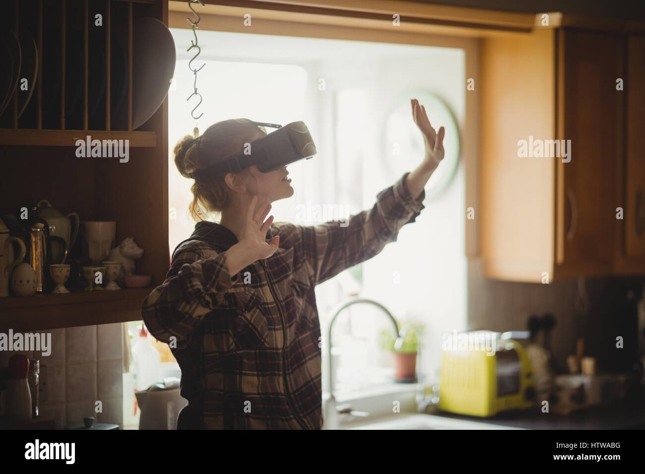 Woman experiencing virtual reality headset in kitchen - Stock Image