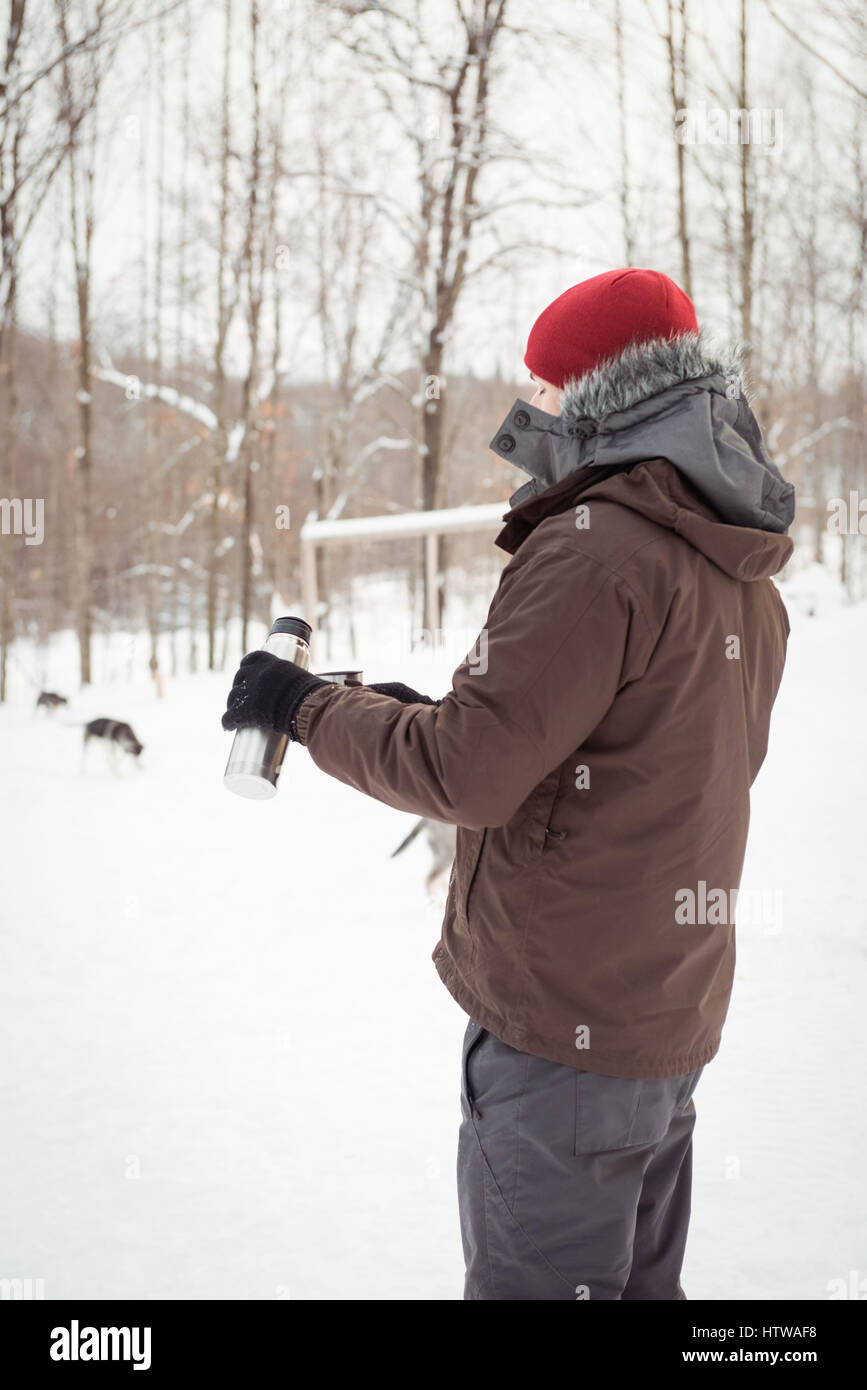 Musher pouring hot drink from thermos - Stock Image
