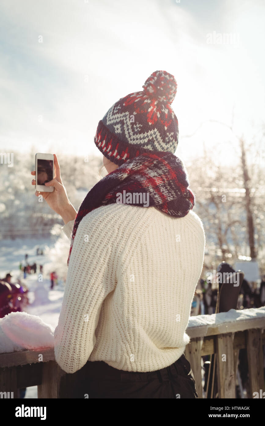 Woman taking a photograph using mobile phone at ski resort - Stock Image