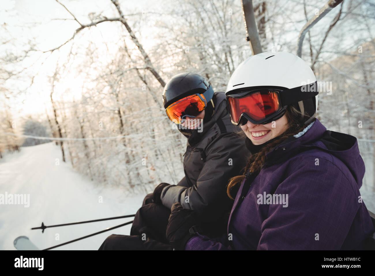 Happy skier couple sitting at the ski resort - Stock Image