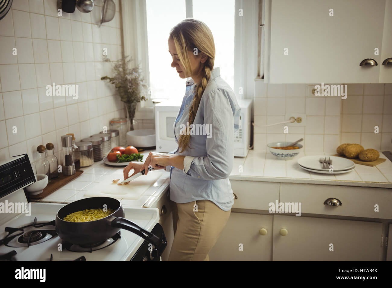 Woman preparing noodles in kitchen - Stock Image