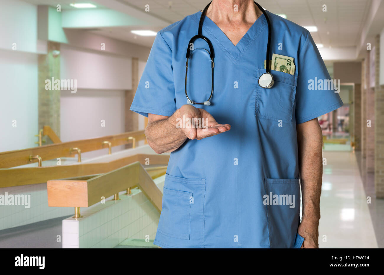 Senior doctor in scrubs asking for payment - Stock Image