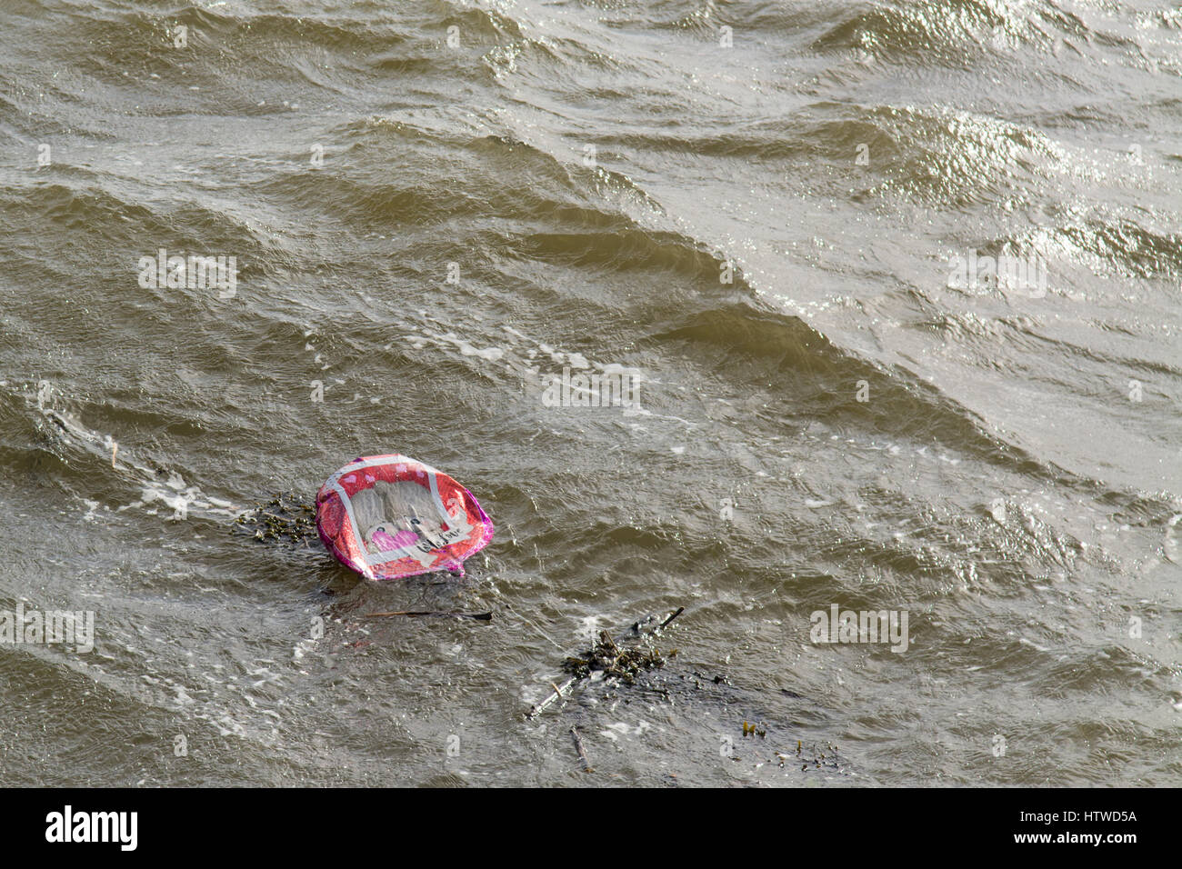balloon litter - foil balloon floating in the sea entangled in seaweed - valentines balloon ironically says 'with - Stock Image