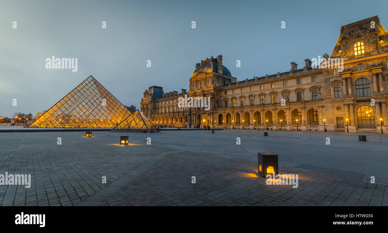 The courtyard of the Louvre (Pyramide du Louvre) at dusk / evening without people or tourists. - Stock Image