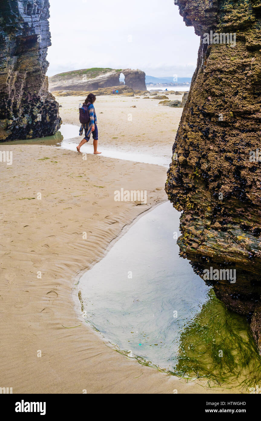 Female solo traveler at Beach of the Cathedrals Natural Monument at Ribadeo municipality, Lugo province, Galicia, - Stock Image
