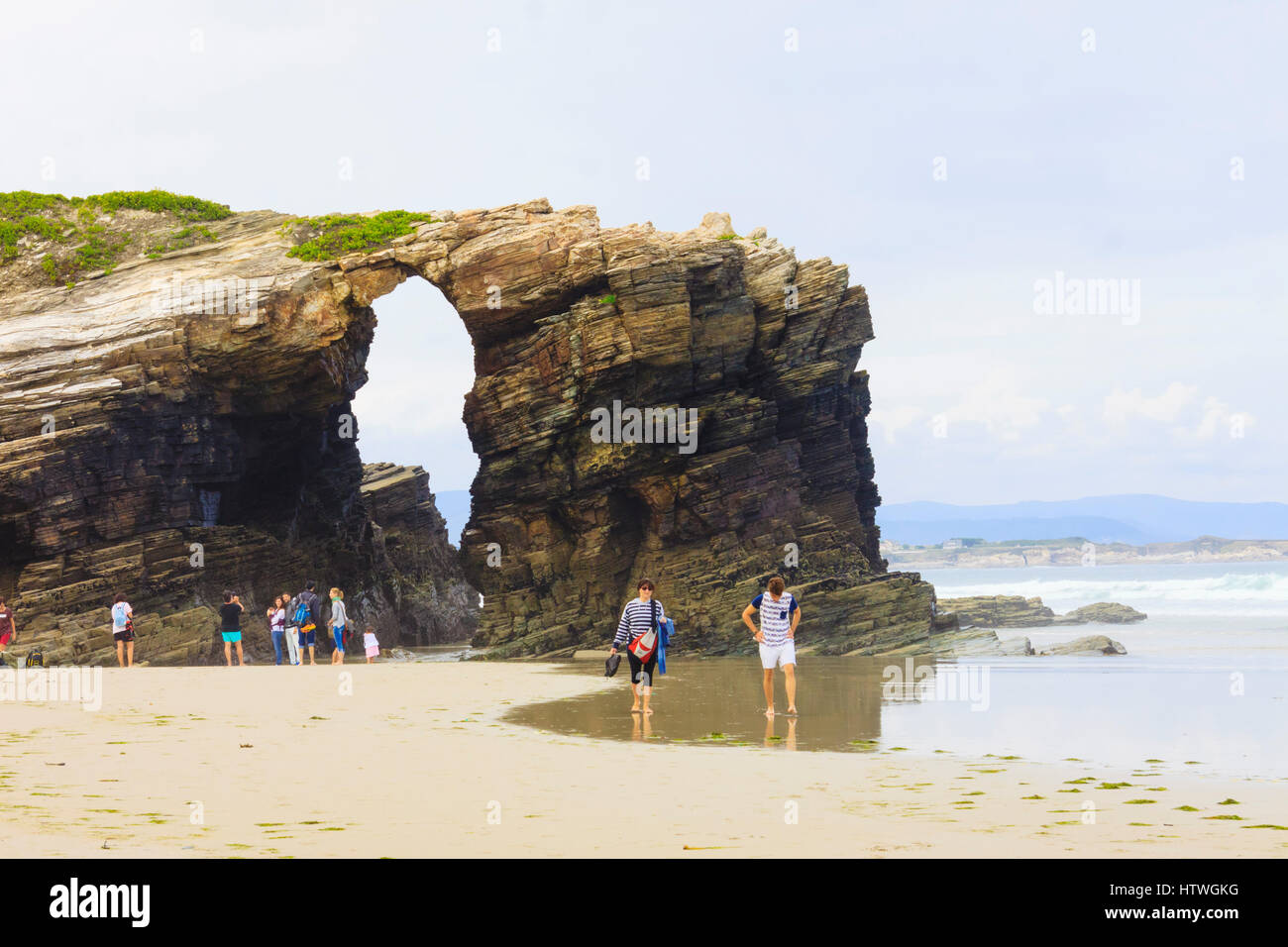 Tourists by a stone arch at Beach of the Cathedrals Natural Monument at Ribadeo municipality, Lugo province, Galicia, - Stock Image