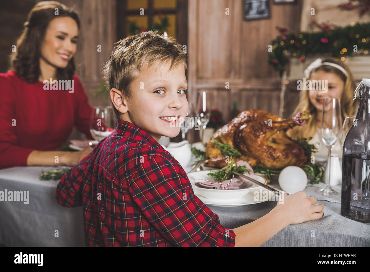 Happy family sitting at holiday table at Christmas time - Stock Image