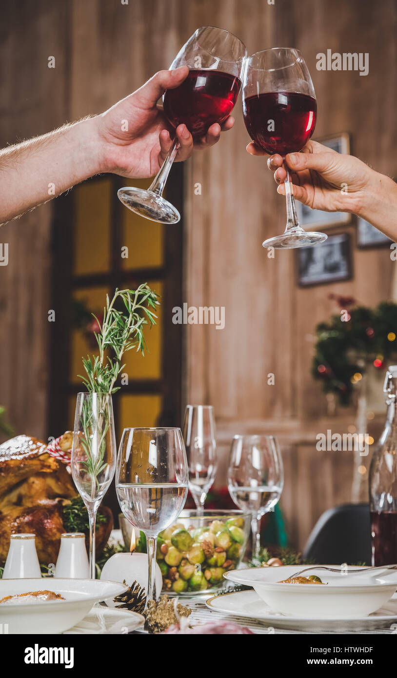 Partial view of couple toasting glasses of red wine at Christmas dinner - Stock Image