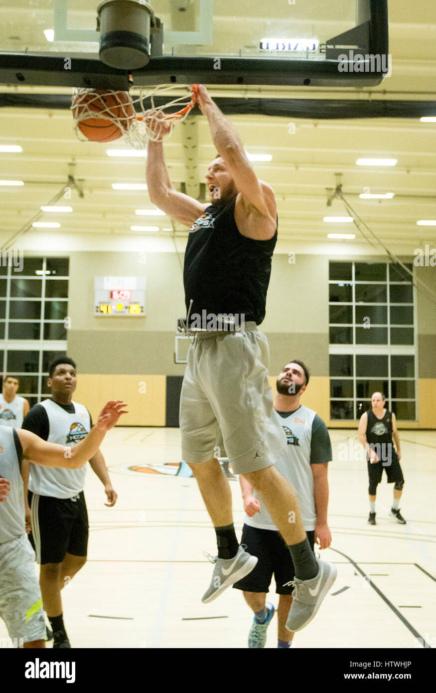 A basketball player dunking a ball - Stock Image