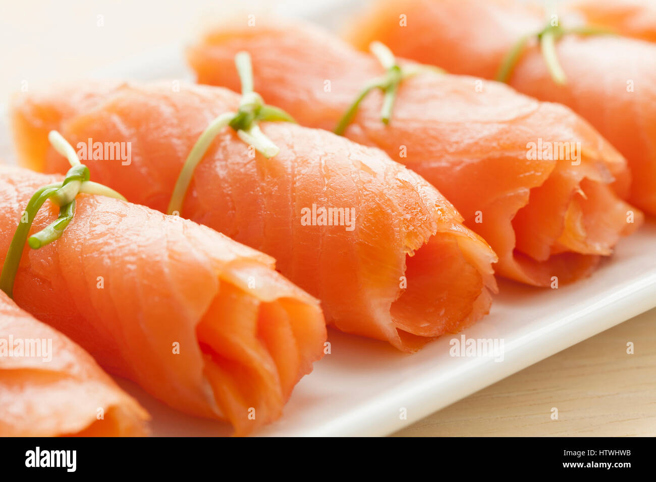 Rolls of smoked salmon with chives as a snack - Stock Image