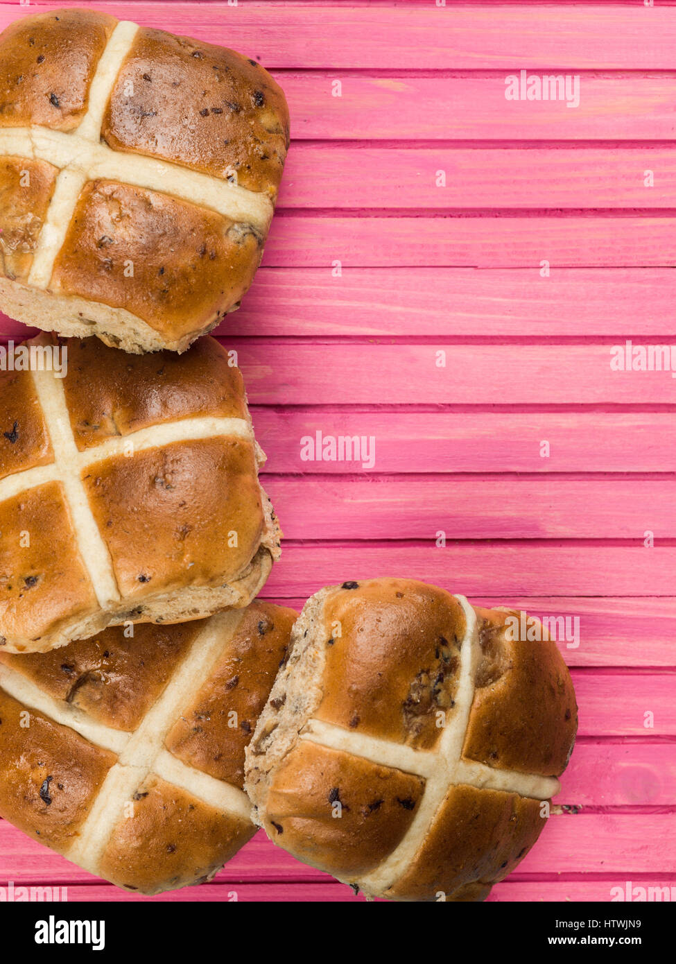 Four Hot Cross Buns Against a Pink Background - Stock Image