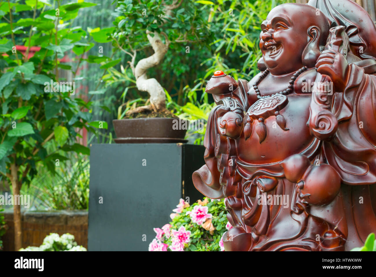 Laughing Buddha Statue In A Chinese Themed Garden Stock Photo Alamy