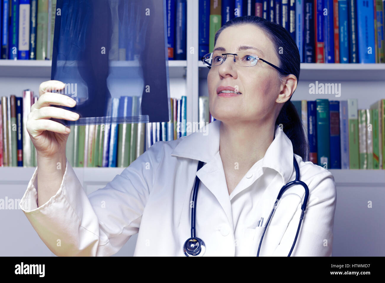 Female doctor or radiologist with stethoscope and an x-ray of a foot in hand as seen through a webcam, blue filter - Stock Image