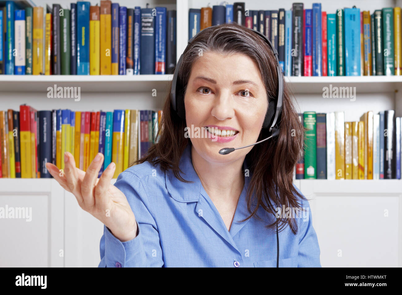 Friendly middle aged woman with headset and a blue shirt in a library, explaining something via the internet, telesales Stock Photo