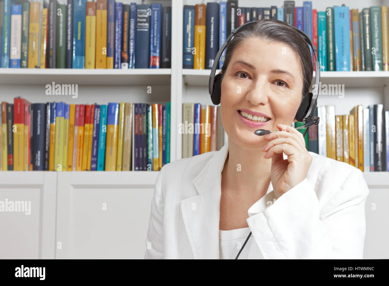 Friendly smiling mature woman with headphones and white blazer in a library, talking with someone via a video call, Stock Photo