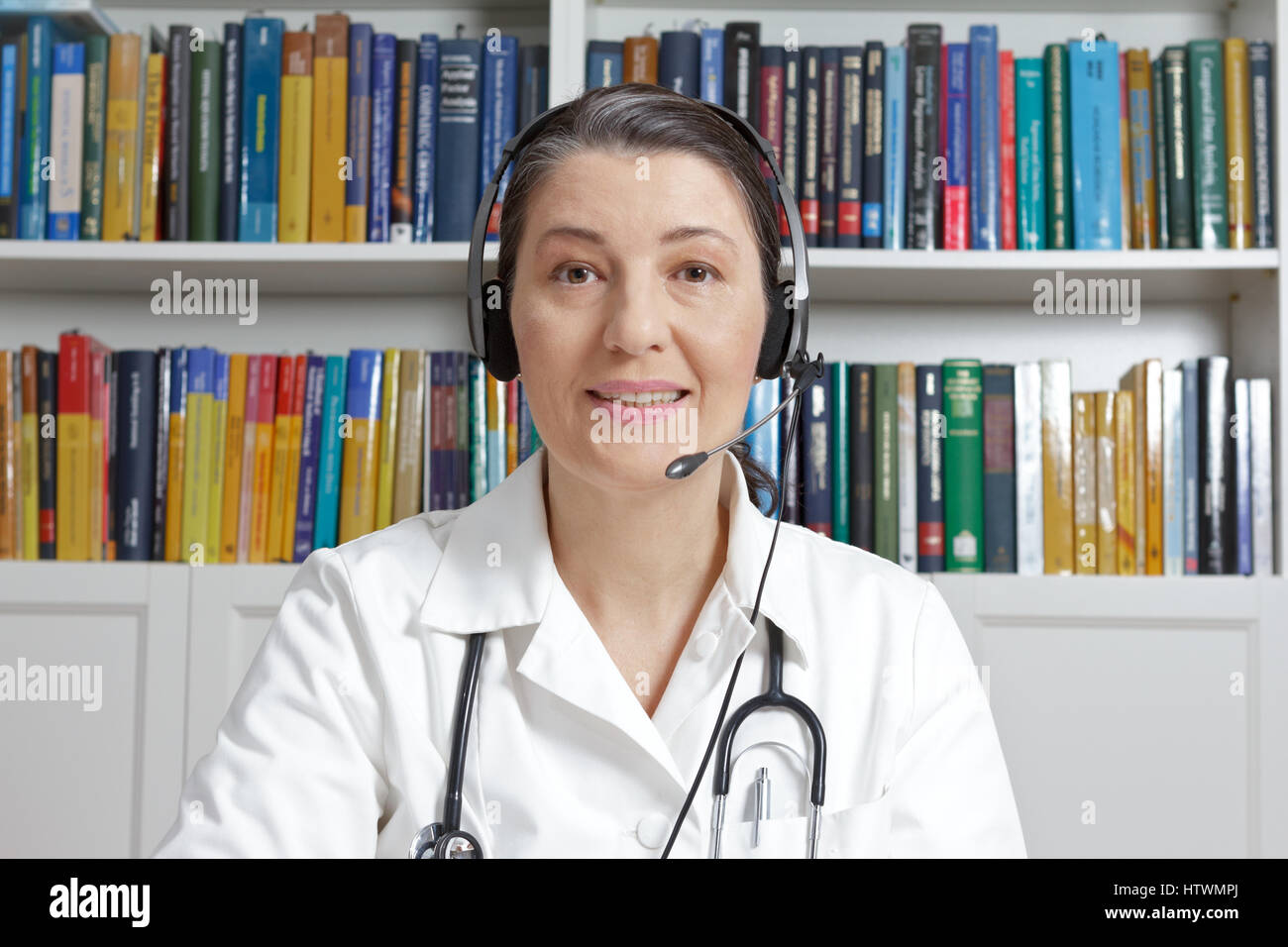 Doctor or general practitioner with headset in surgery office talking online with a patient, as seen through a webcam, Stock Photo