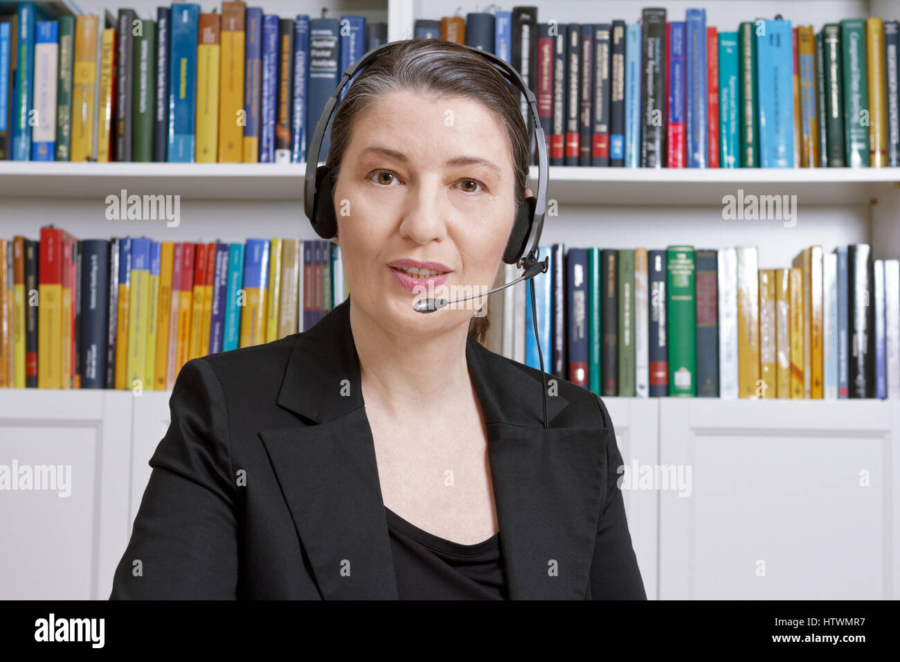 Friendly middle aged woman with headphones and black blazer in an office with lots of books, talking via the internet, - Stock Image