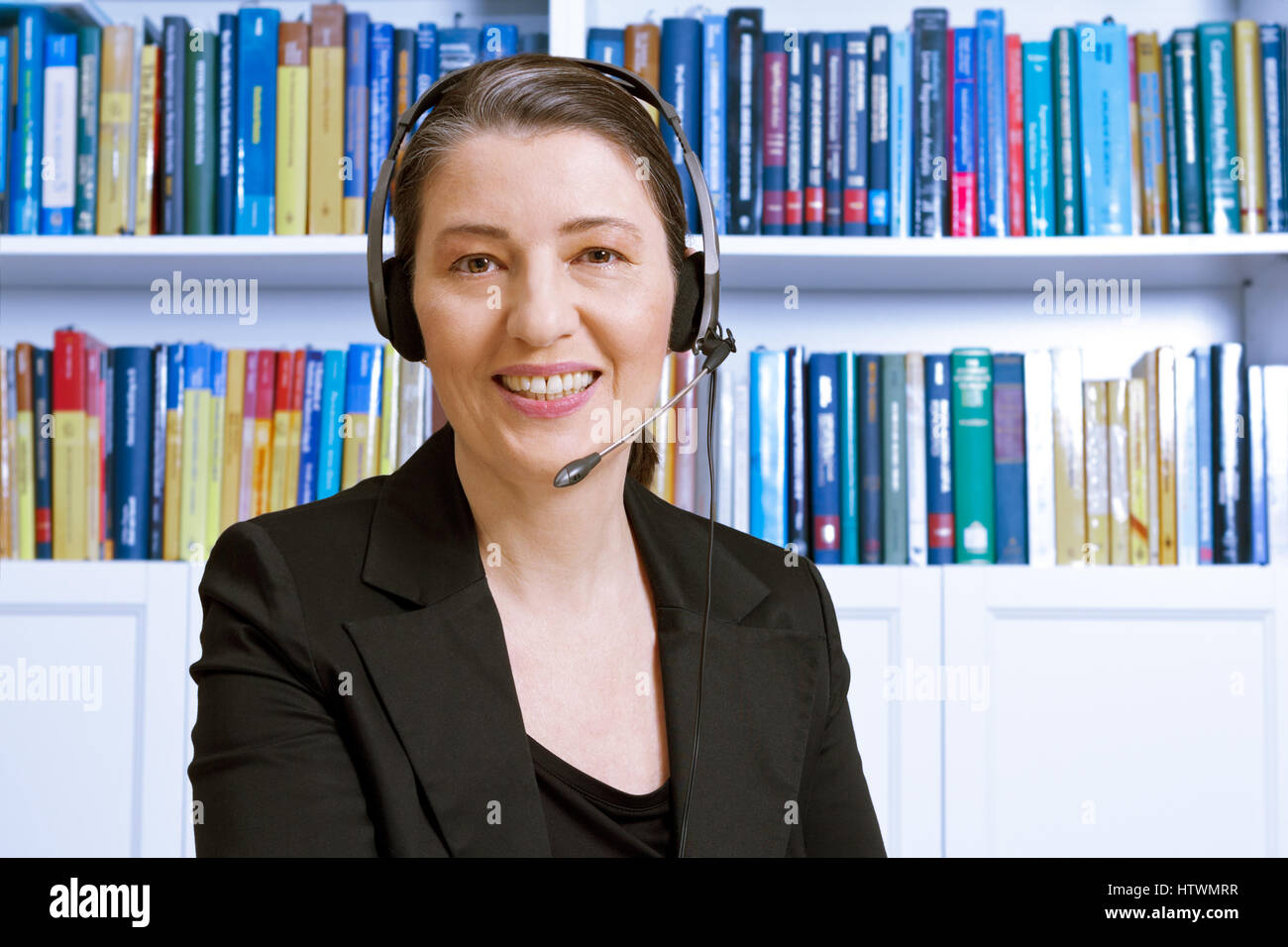 Friendly smiling middle aged woman with headset and black blazer in an office with lots of books, lawyer or accountant, - Stock Image