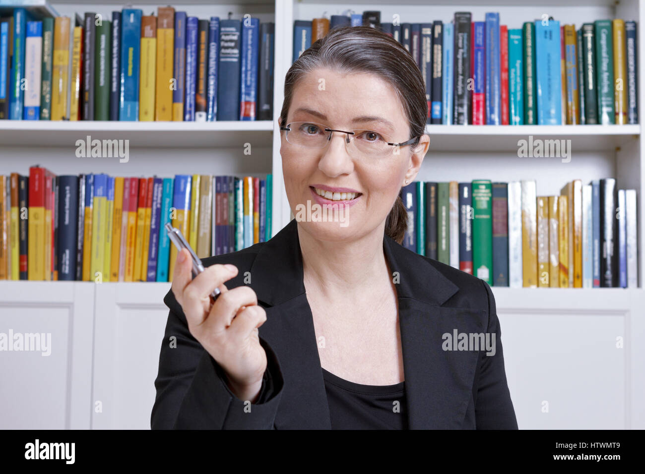 Friendly middle aged woman with black blazer in an office with lots of books explaining something during a lesson, - Stock Image