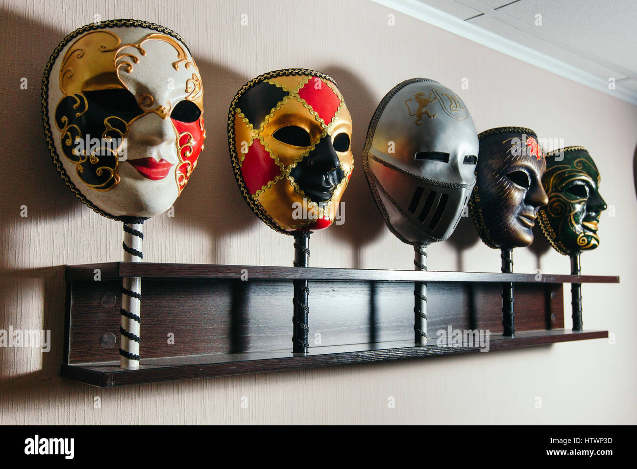Masks for playing in the mafia stand on the shelf. - Stock Image