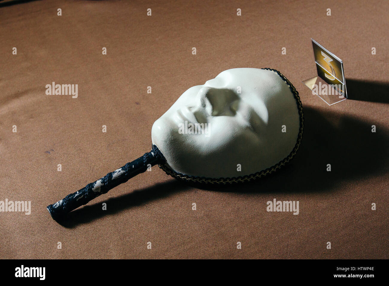 White mask for playing in the mafia on the table. - Stock Image