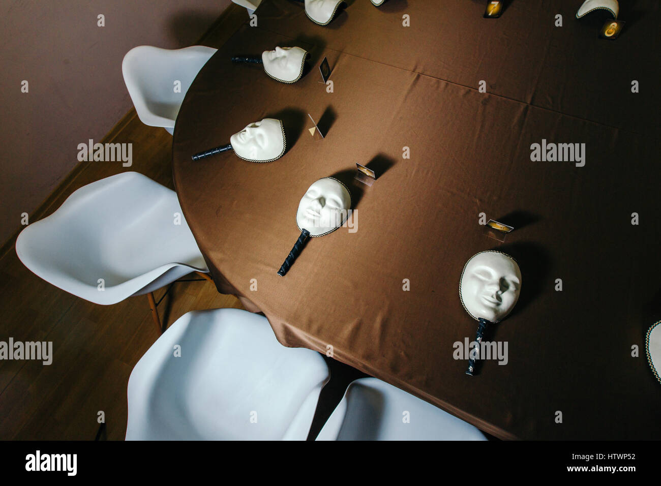 White masks for playing in the mafia on the table. - Stock Image