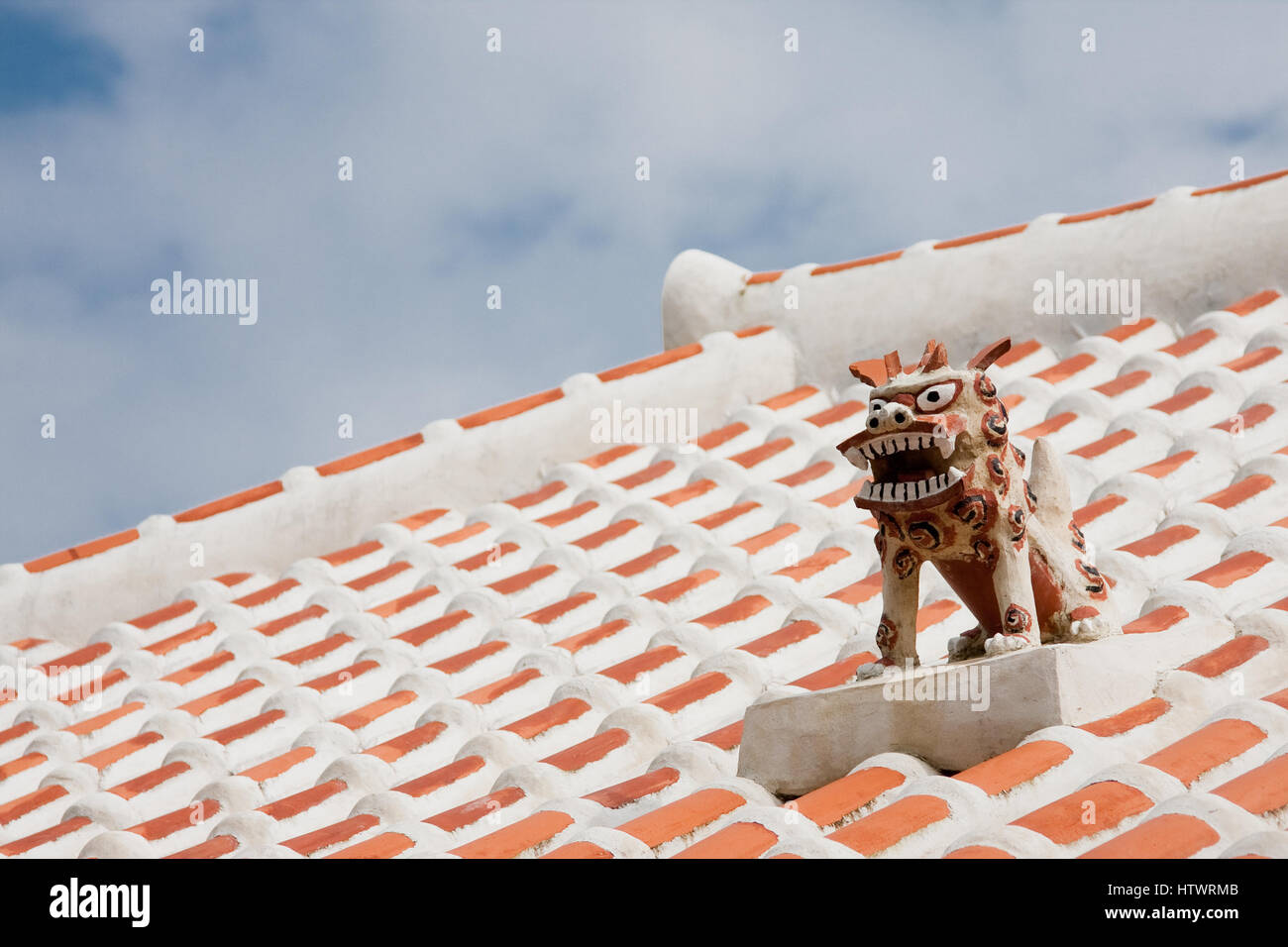Shisa guardian dog on the roof top of a traditional Okinawan home. They are found on almost all roof tops or entrances - Stock Image