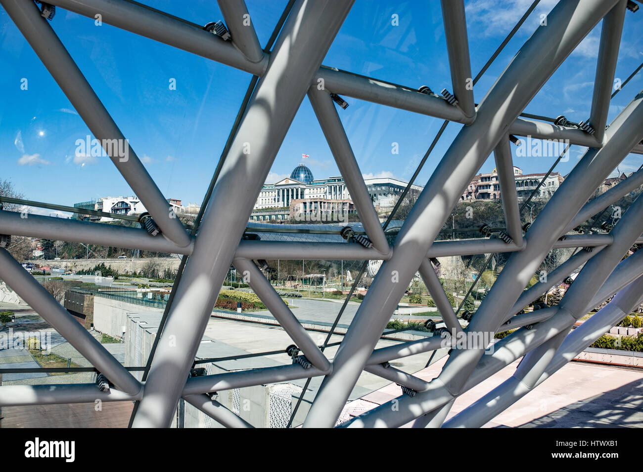 View on Tbilisi from the Bridge of Peace - a bow-shaped pedestrian bridge, steal and glass construction. In the - Stock Image