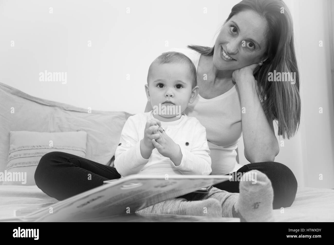 Pregnant mother  and her son are reading a book. - Stock Image