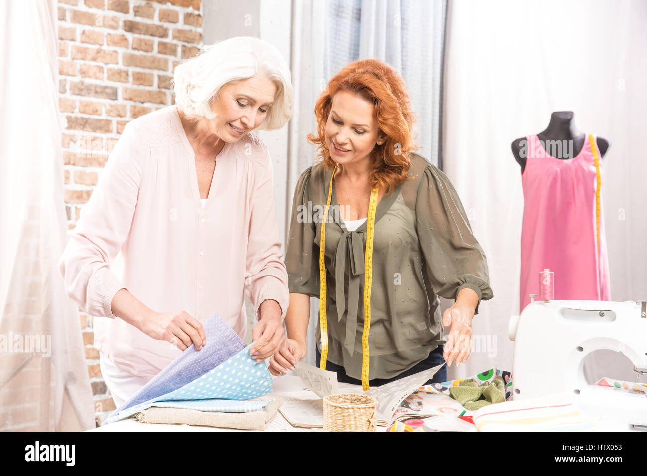 Two smiling seamstresses - Stock Image
