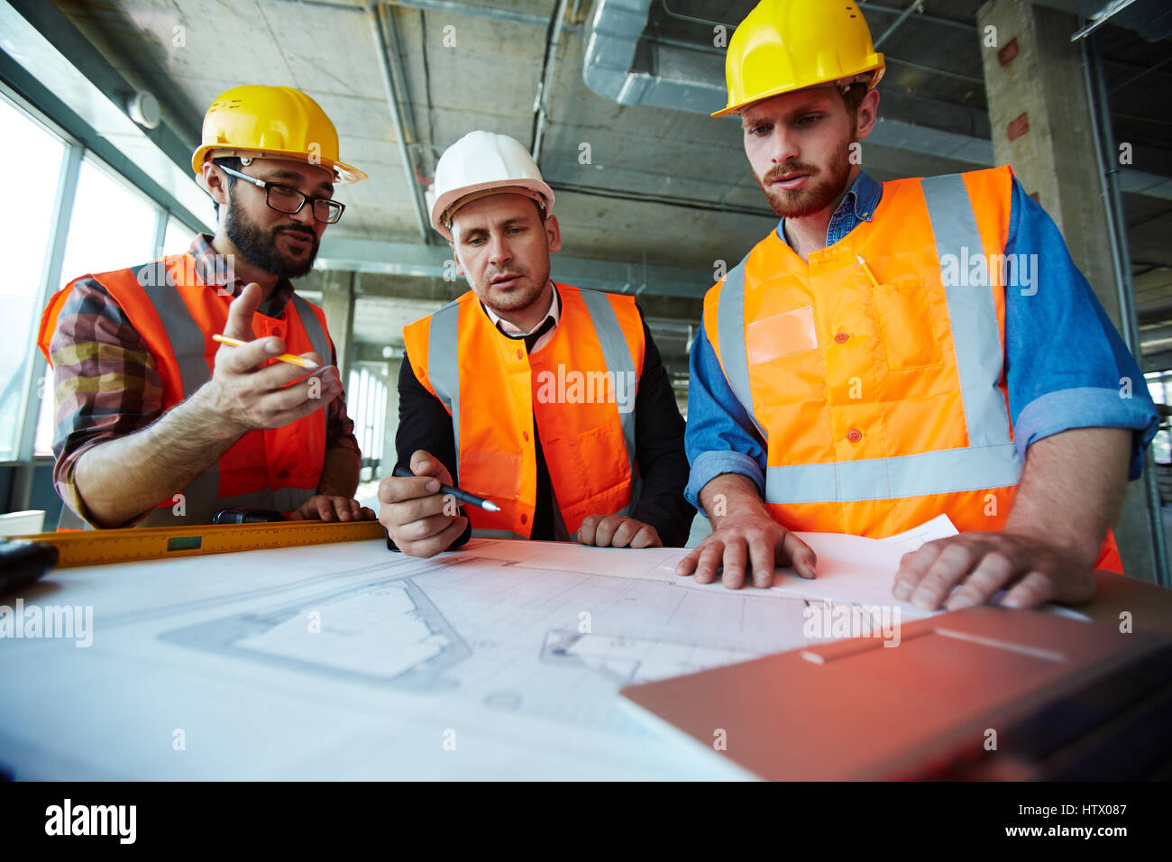 Supervisors discussing sketch of building - Stock Image