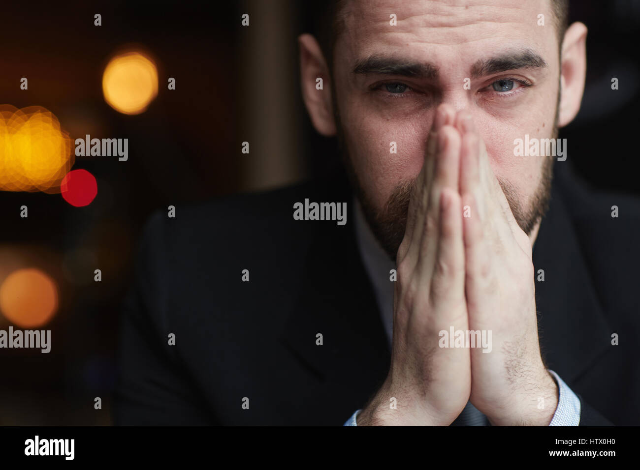 Portrait of modern bearded businessman looking at camera with red teary eyes, stressed and tired against black background, - Stock Image