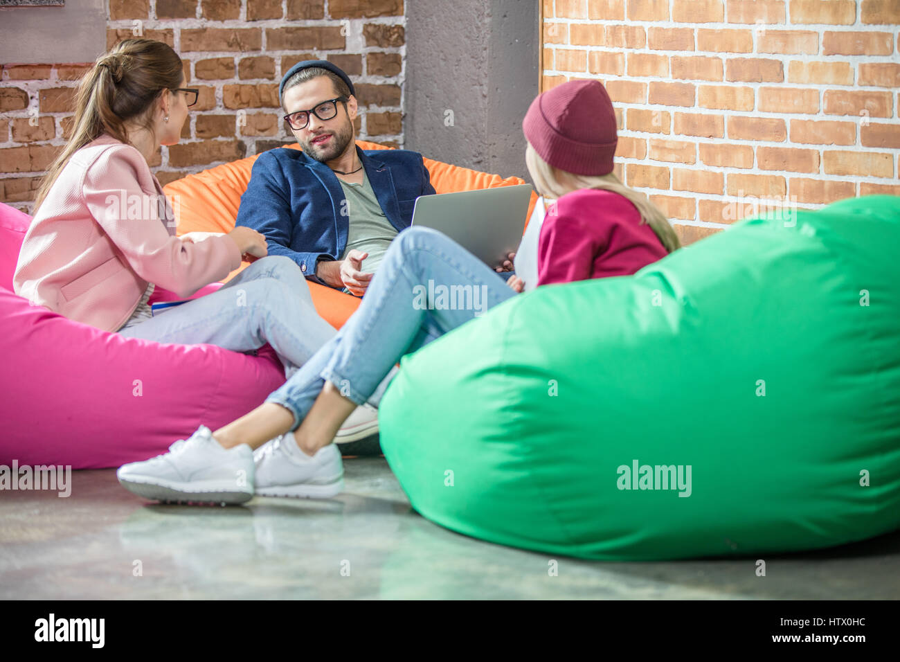 People in bean bag chairs - Stock Image