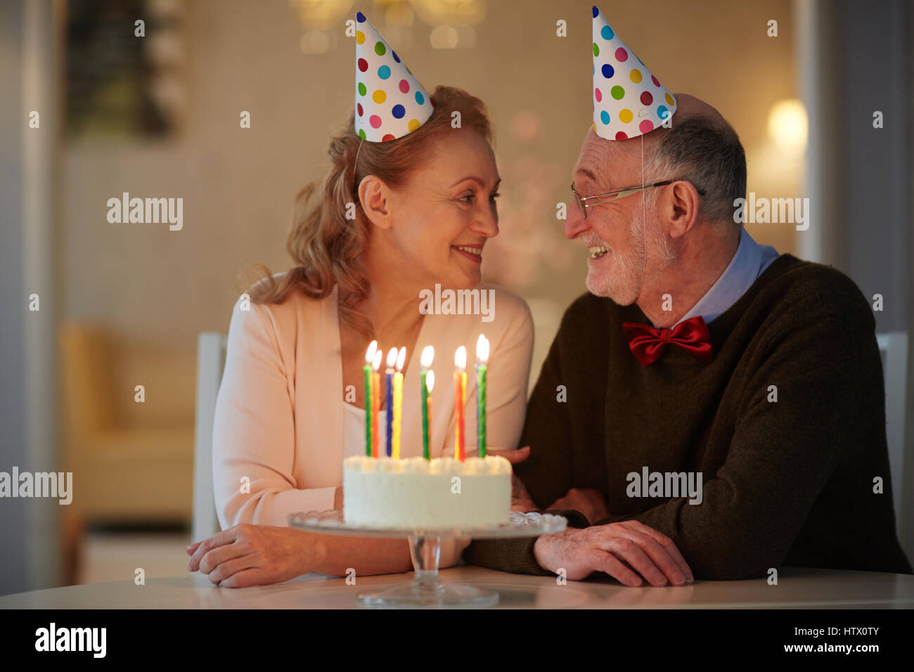 Portrait of loving senior couple celebrating birthday together sitting at table with cake and wearing party hats - Stock Image
