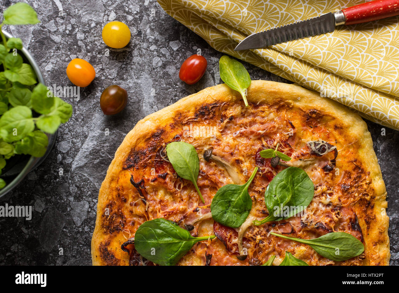 Homemade Pizza with Cheese, Ham, Salami, Baby Spinach and Shimeji Mushrooms. Fresh Baked Italian Food Ready to Eat. - Stock Image