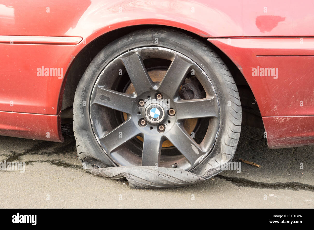 flat burst tyre tire with severe kerbing curbing damage to alloy wheel wheels - Stock Image