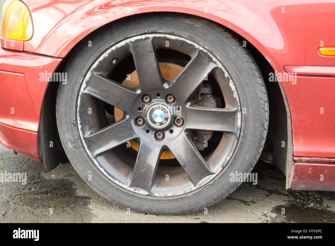 kerbing curbing damage to alloy wheels - Stock Image