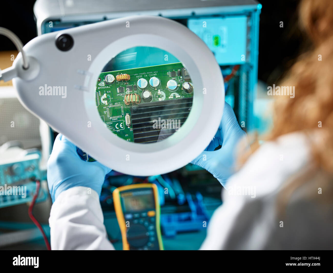 Engineer with white lab coat examining graphics card, looking through magnifying glasses to board, Austria - Stock Image