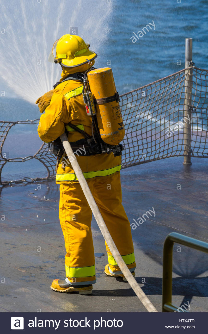 A firefighter, clad in turnout gear, aims a fan of water from a firehose off the back of a Washington State Ferry - Stock Image