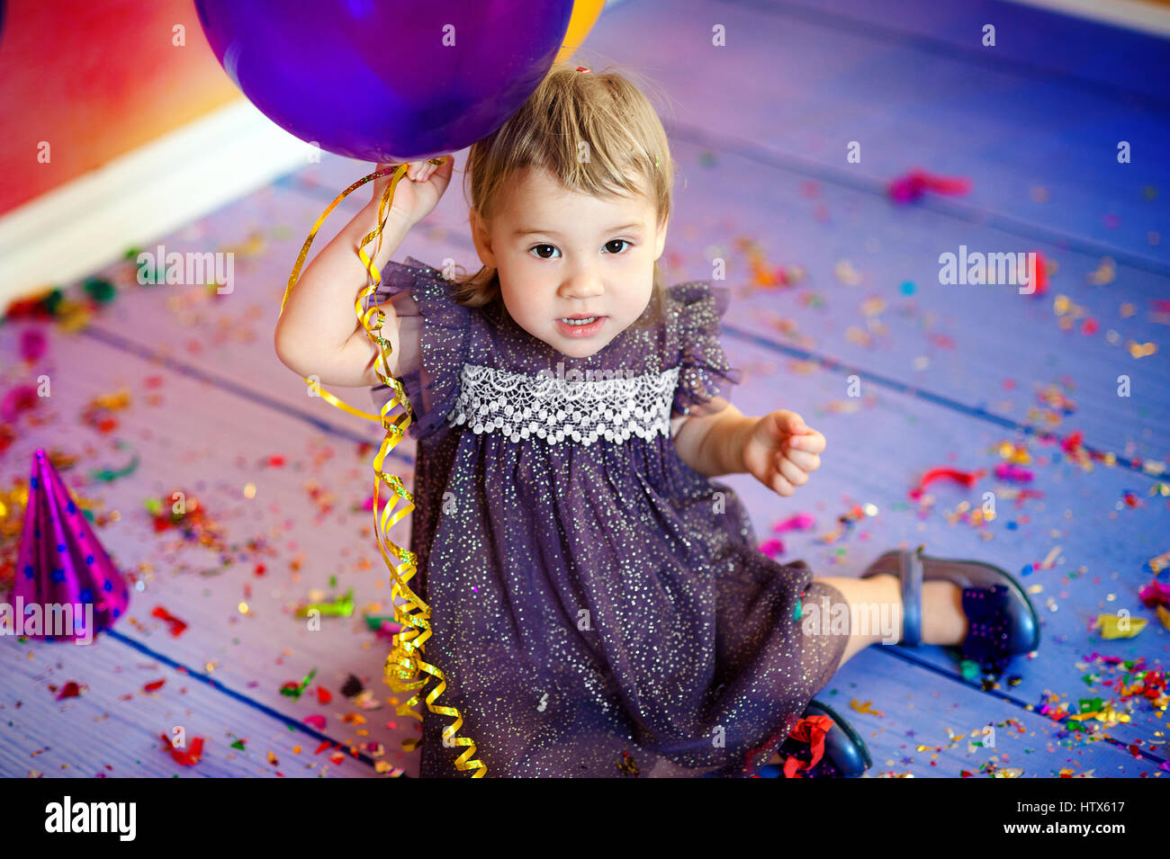 Cute baby girl 1-2 year old sitting on floor with pink balloons in room. Birthday party. Celebration. Happy birthday - Stock Image