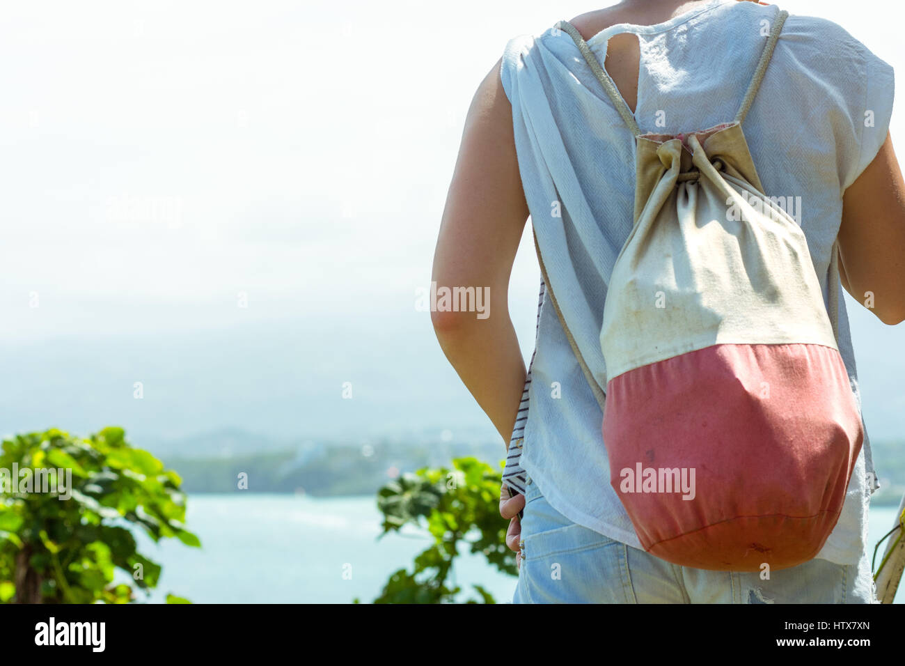 Rear view of a young woman wearing a back pack looking over a cliff and sea view. - Stock Image