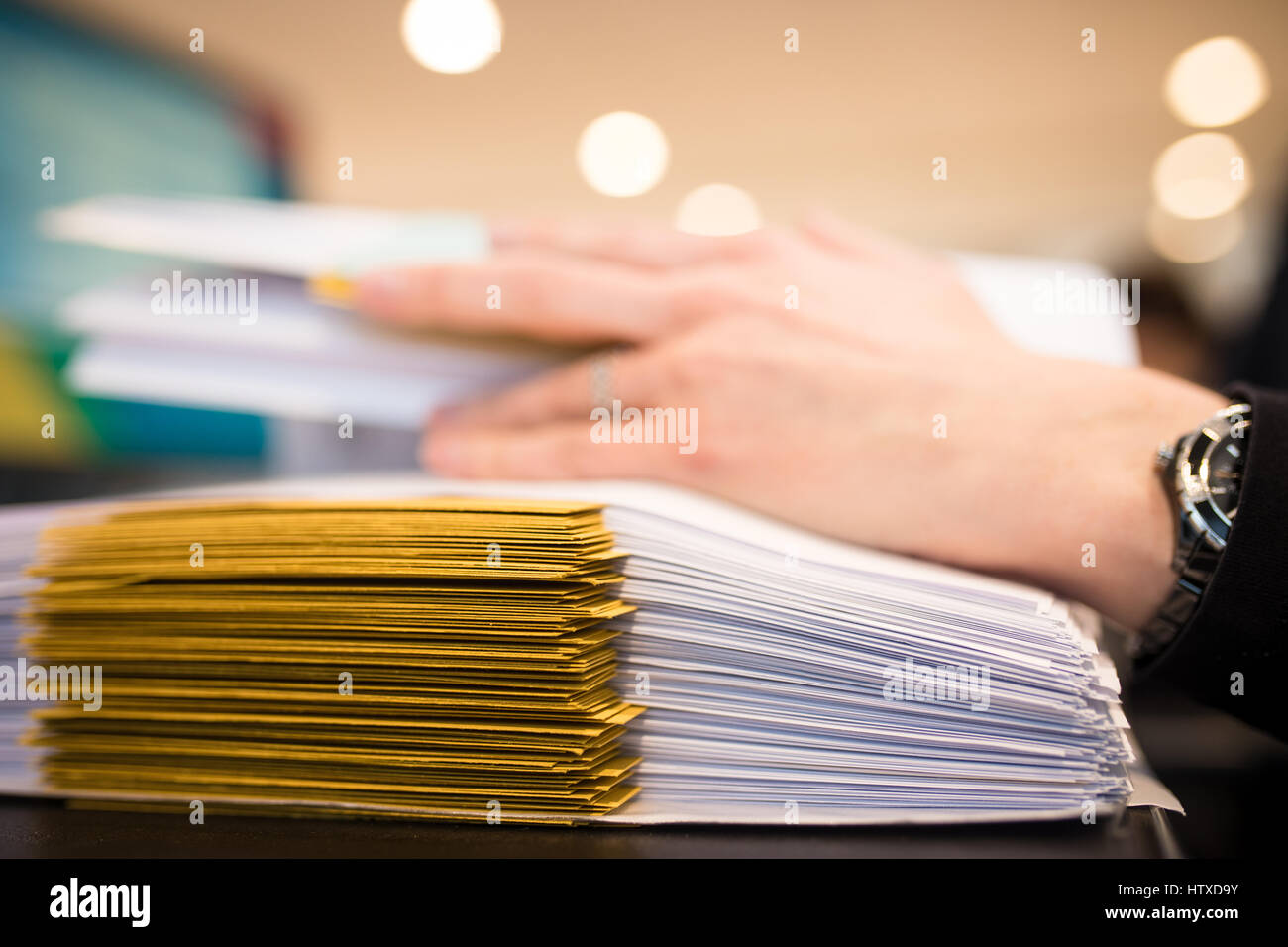 Close-up of female hand with dossiers at the office . Working on stack of files. Shallow DOF - Stock Image