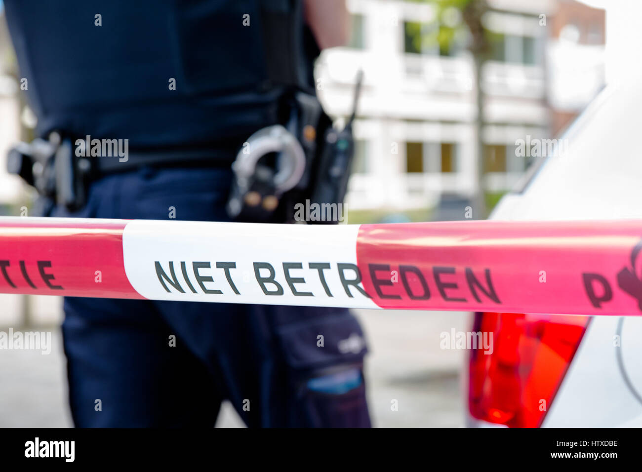 Dutch police line do not cross. Red plastic tape and  police officer, gun belt, handcuffs and gun on a crime scene. - Stock Image