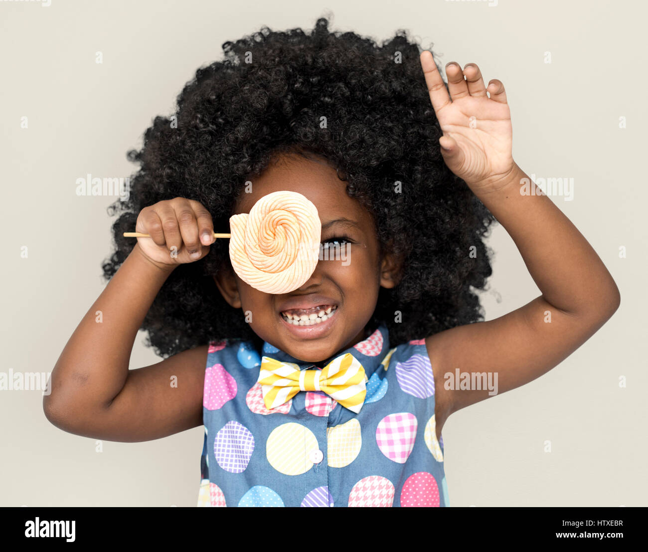 African Descent Child Lollipop Candy - Stock Image